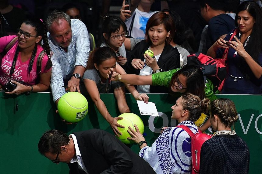 Above:  Excited fans seeking autographs as well as wefies from Romania's Simona Halep after her match win on Monday at the WTA Finals, one of the premier events on the annual sporting calendar.