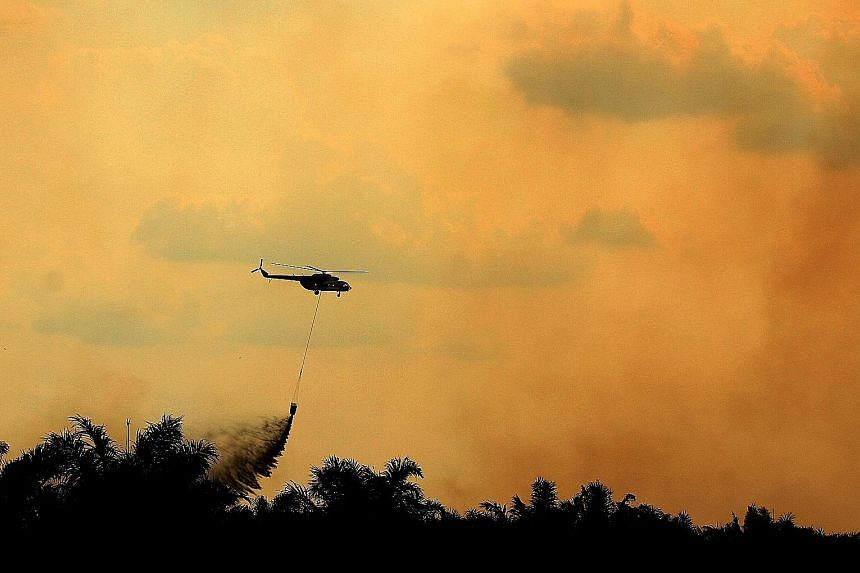 A helicopter operated by the Indonesian National Disaster Management Agency conducting water bombing operations to put out fires in Ogan Ilir, South Sumatra, in August.