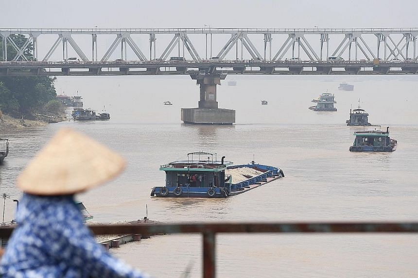 Boats on Hanoi's Red River transporting sand in August. Vietnam needs about 100 million cubic metres of sand every year for construction projects. With over-exploitation threatening to deplete the domestic supply of natural sand, the authorities are