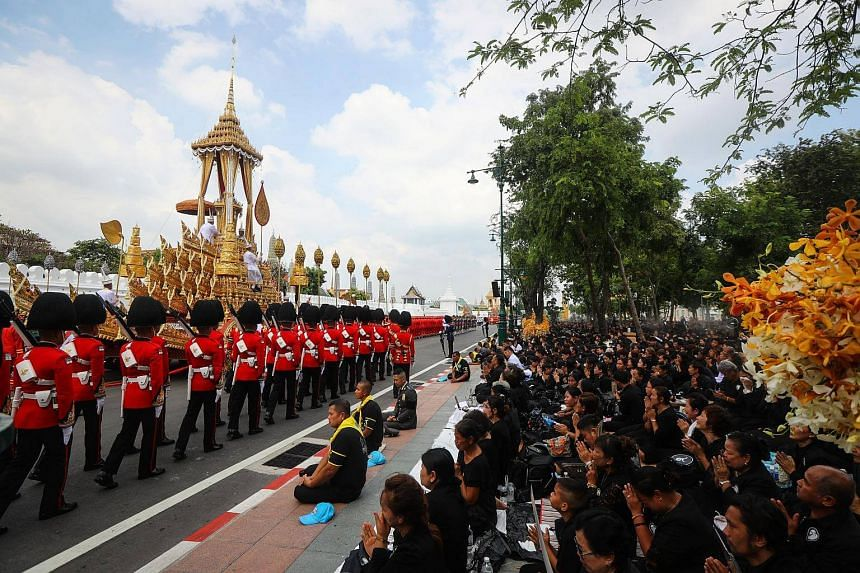 Thai mourners pay their respects as royal military officers pull the Great Victory Royal Chariot carrying the royal urn of the late Thai King Bhumibol Adulyadej, from the Grand Palace to the Royal Crematorium at Salam Luang in Bangkok.
