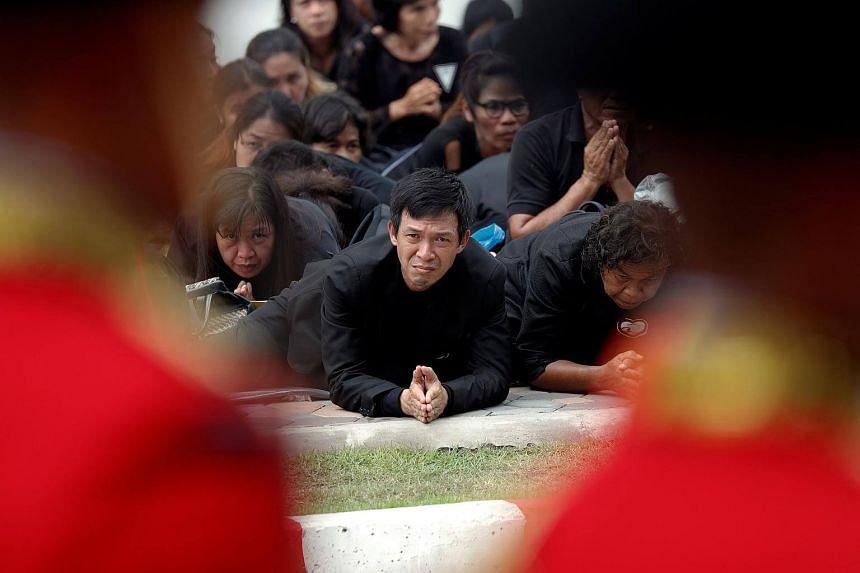 Mourners react as Thailand's King Maha Vajiralongkorn passes by during the royal cremation procession of late King Bhumibol Adulyadej at the Grand Palace in Bangkok.
