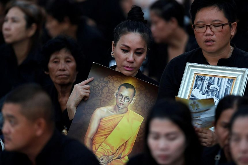 Mourners wait for the start of the funeral procession for Thailand's late King Bhumibol Adulyadej before the Royal Cremation Ceremony in front of the Grand Palace in Bangkok.