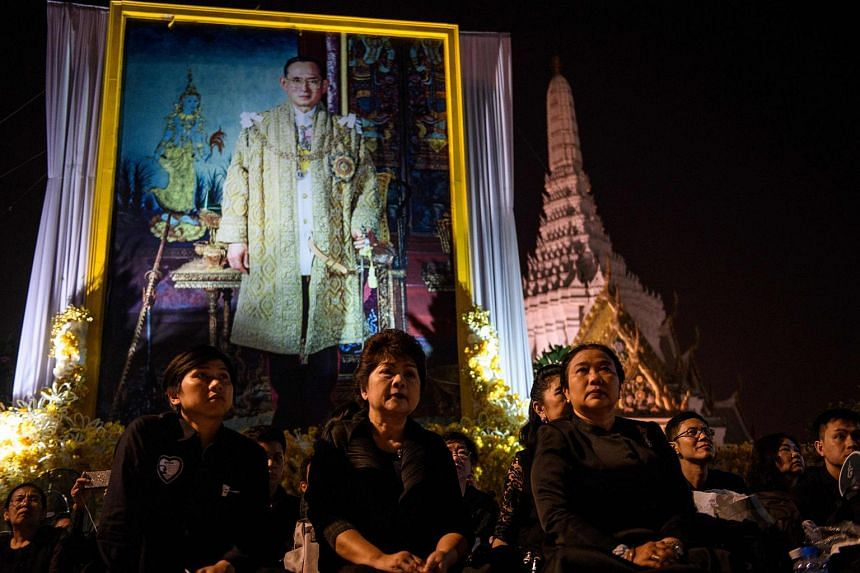 Mourners gather under a portrait of the late Thai King Bhumibol Adulyadej as they wait for his funeral procession to take place outside the Grand Palace in Bangkok.