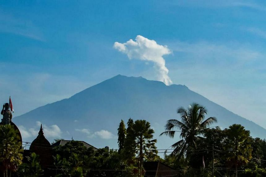 Mount Agung volcano spews steam and smoke into the air as seen from Bangli on Indonesia's resort island of Bali on Oct 23, 2017.