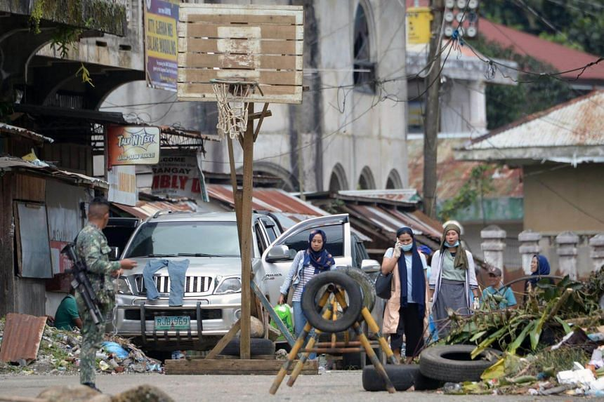 A soldier keeps watch as residents returning to inspect their homes walk past near the battle area of Mapandi in Marawi, on the southern island of Mindanao, on Oct 24, 2017.