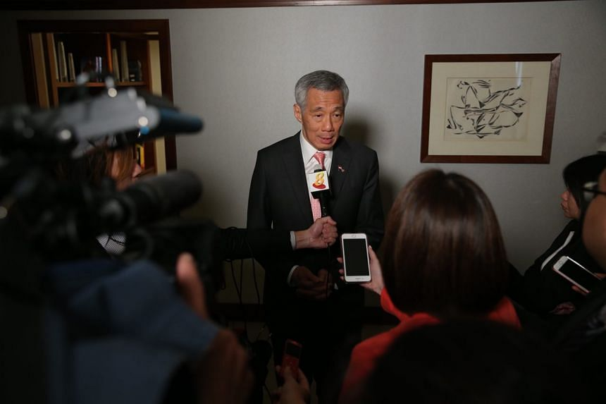 PM Lee Hsien Loong speaks to reporters during the wrap-up interview.