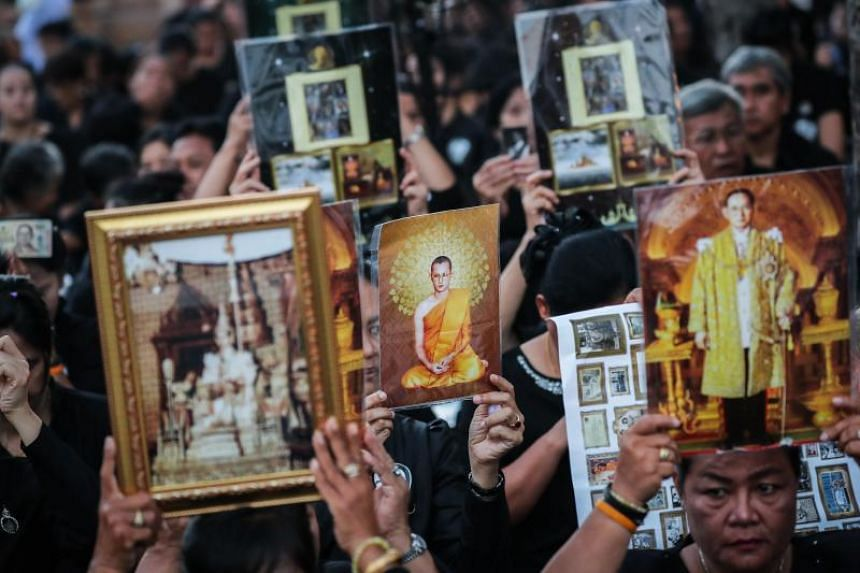 Thai mourners hold pictures of the late Thai King Bhumibol Adulyadej as they wait for the royal cremation ceremony outside the Royal Palace in Bangkok.