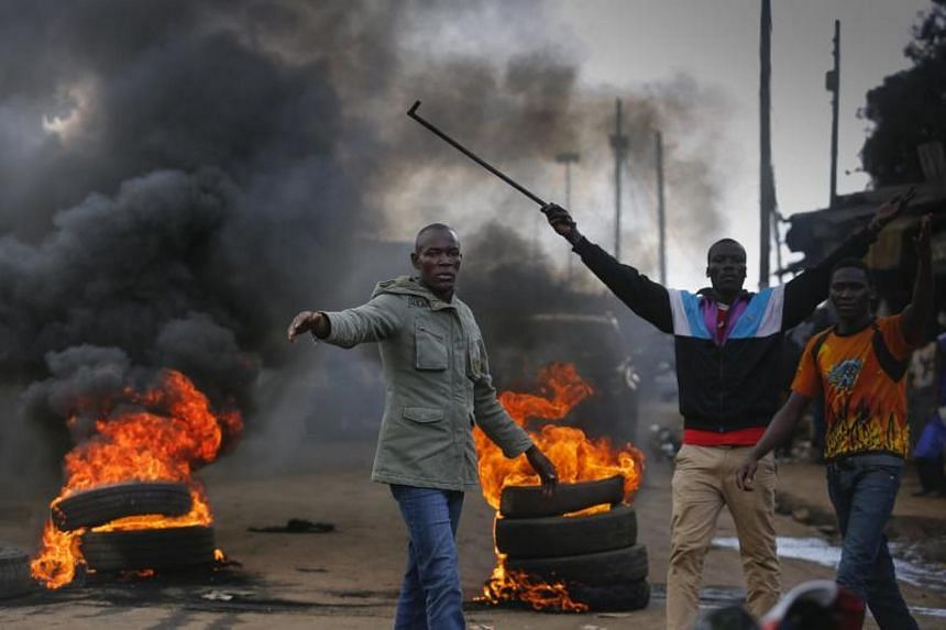 Supporters of the opposition coalition the National Super Alliance (NASA) and its presidential candidate Raila Odinga react in front of a burning barricade they set up to block vehicles from delivering electoral materials to the polling stations.