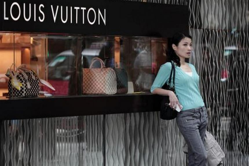 This picture taken on April 23, 2013 shows a Chinese woman leaning on a Louis Vuitton shop display window in Hong Kong.