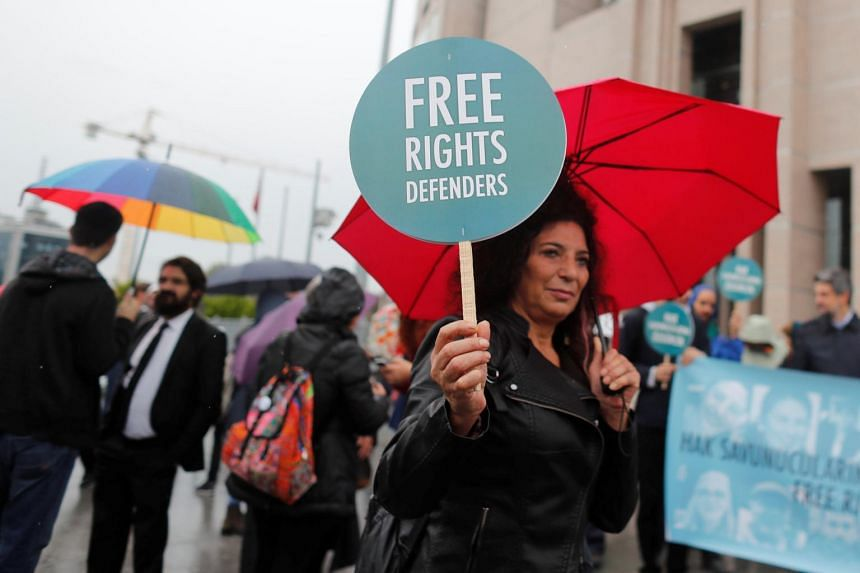 Rights activists gather in front of the Justice Palace during the opening hearing of the trial of eleven human rights activists accused of terrorism charges, in Istanbul, Turkey.