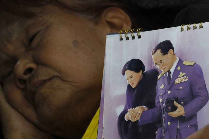 A mourner holding a portrait of King Bhumibol and Queen Sirikit near the Grand Palace yesterday.