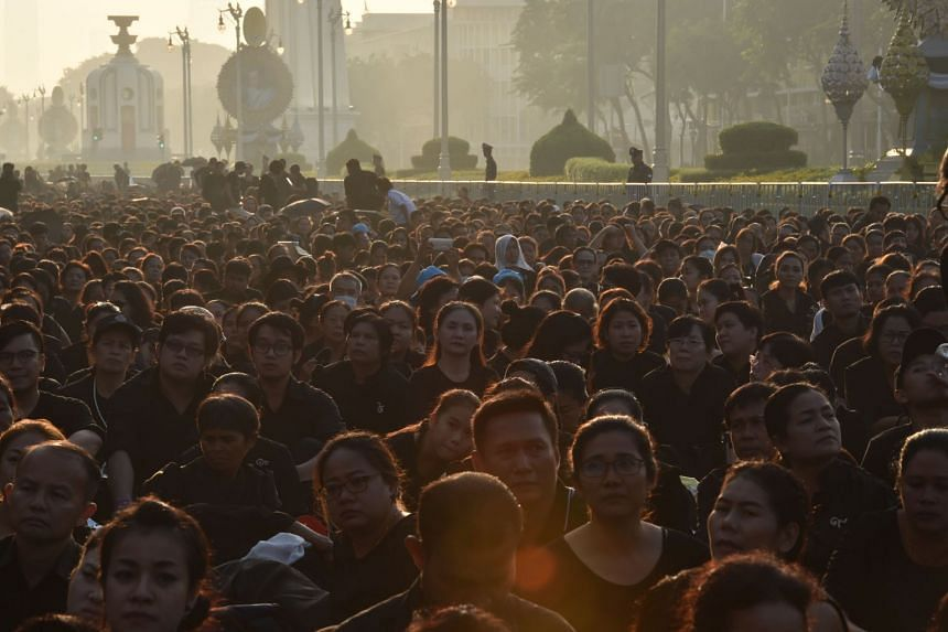 Mourners wait for the funeral procession of the late Thai King Bhumibol Adulyadej to take place in Bangkok.