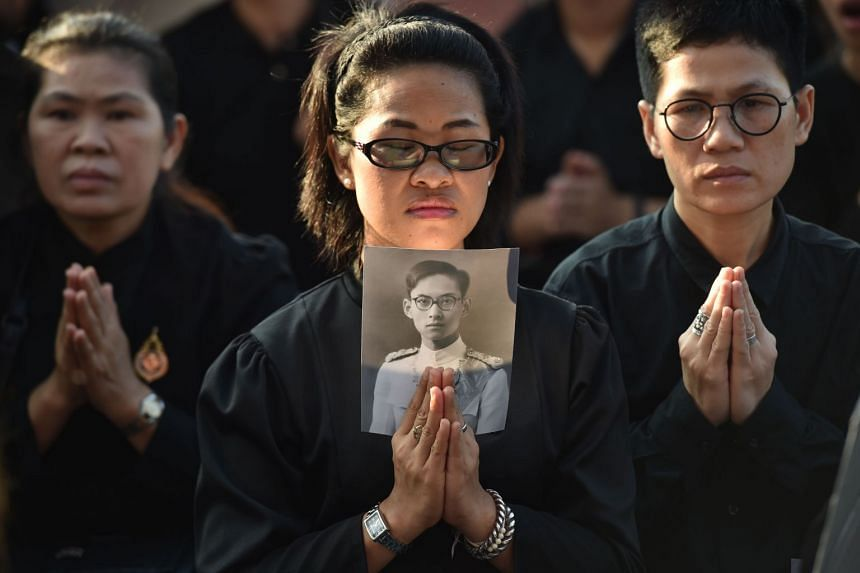 A mourner holds an image of the late Thai King Bhumibol Adulyadej as she waits for his funeral procession to take place in Bangkok.
