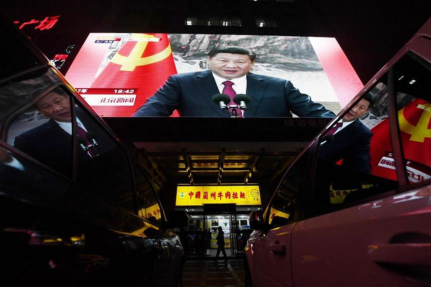 People walk outside a shop below a screen showing news coverage about Chinese President Xi Jinping, in Beijing.