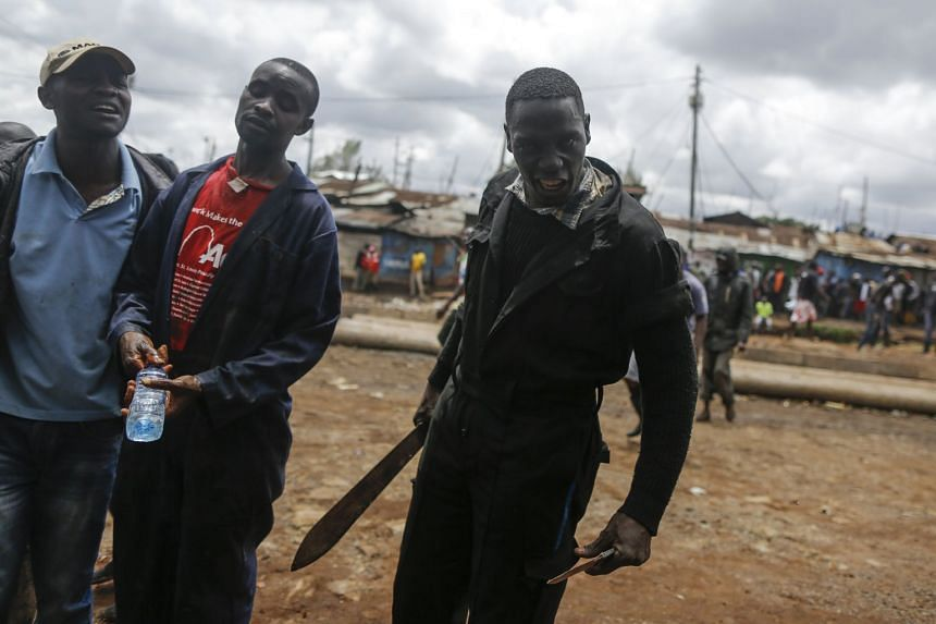 A supporter of the opposition coalition warns a photographer as he holds a machete, Oct 26, 2017.