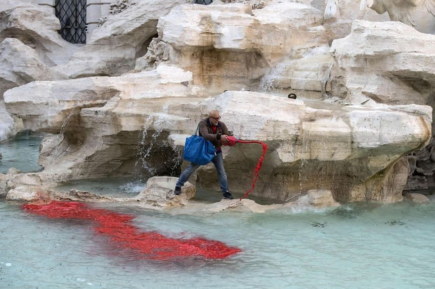 A man identified as Graziano Cecchini pours red dye into the water of the Trevi fountain.