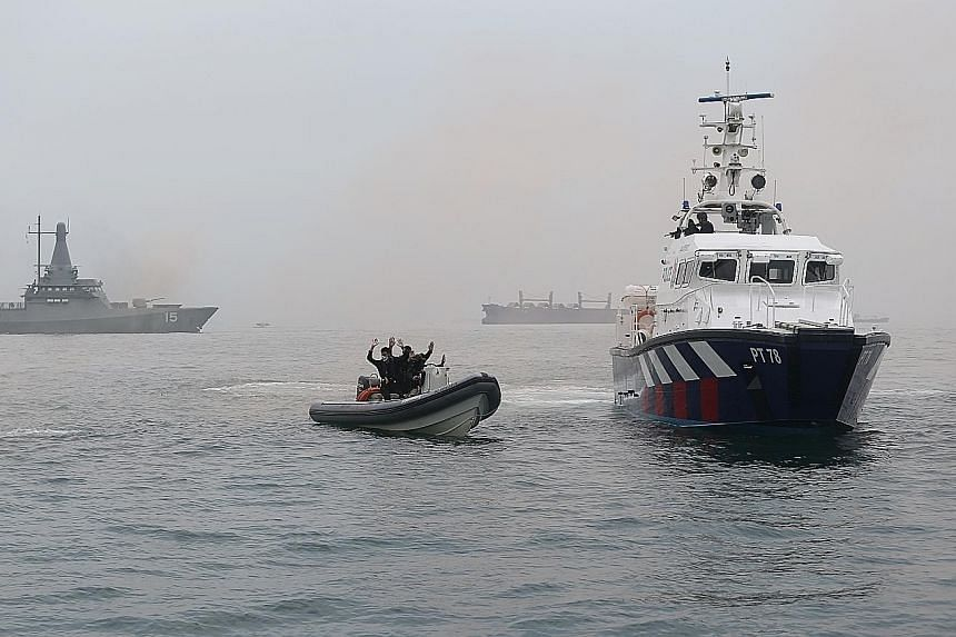 "A Republic of Singapore Navy Littoral Mission Vessel (background, far left), and the Police Coast Guard's patrol interdiction boat (at right) intercepting the mock terrorists' speedboat. The exercise scenario involved ""terrorists"" in speedboats, who"