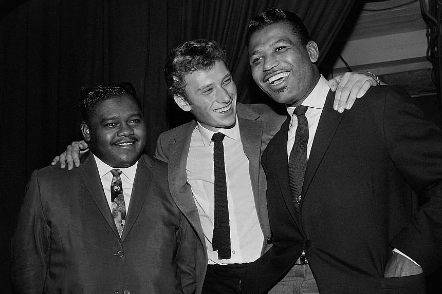 Fats Domino (far left) with French singer Johnny Hallyday (centre) and US boxing champion Ray Sugar Robinson following Domino's performance at the Palais des Sports in Paris on Oct 20, 1962.
