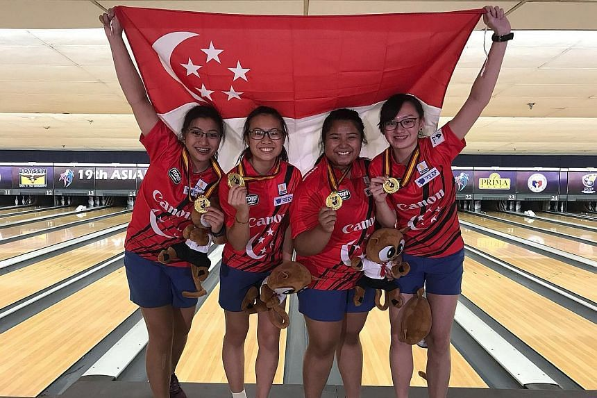 From left: Jermaine Seah, Charlene Lim, Illiya Syamim and Amabel Chua fly the Singapore flag high on the Coronado Lanes alleys in Manila after capturing a much-coveted team gold.