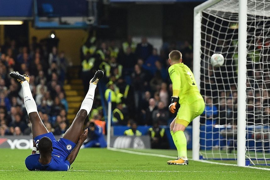 Chelsea's German defender Antonio Rudiger falls on his back after looping a header past Everton goalkeeper Jordan Pickford during their League Cup fourth-round match. Rudiger's goal set Chelsea on course for an eventual 2-1 victory.