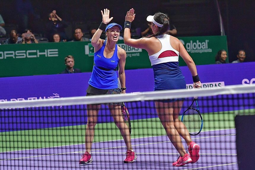 Martina Hingis exchanging high-fives with Chan Yung-jan during their 6-3, 6-2 quarter-final victory over Anna-Lena Gronefeld and Kveta Peschke.