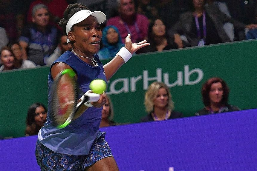 Venus Williams hitting a laboured return to Garbine Muguruza in their White Group match last night. The American came through in straight sets to seal her place in the last four as group runner-up.