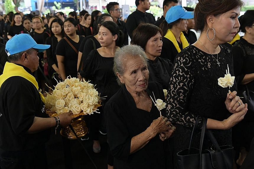 Many of the mourners placed sandalwood flowers in front of the late King's portrait at the Royal Thai Embassy in Orchard Road yesterday. The proceedings in Bangkok were also broadcast live.