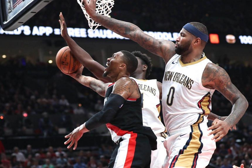 Portland Trail Blazers guard Damian Lillard draws a foul against New Orleans Pelicans forward DeMarcus Cousins (right) in the second half at the Moda Center on Oct 24, 2017.