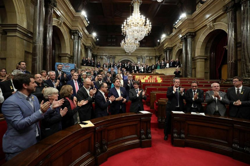 Catalan President Puigdemont and deputies applaud after the Catalan regional Parliament declared independence from Spain in Barcelona on Oct 27, 2017.
