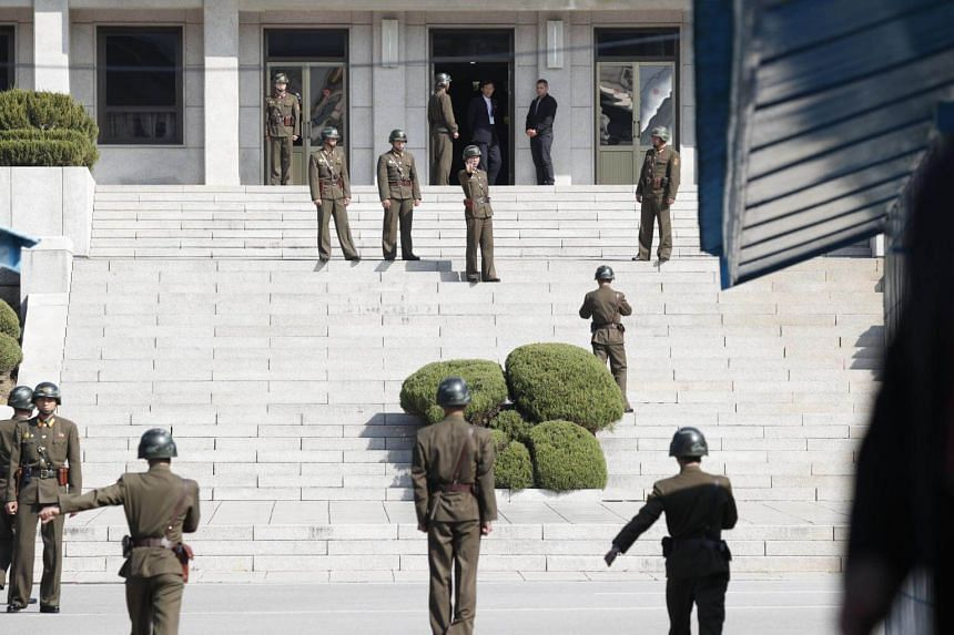 North Korean soldiers (left) look at the South side while US Secretary of Defence Jim Mattis and South Korean Defence Minister Song Young-Moo visit at the truce village of Panmunjom in the Demilitarized Zone on Oct 27, 2017.