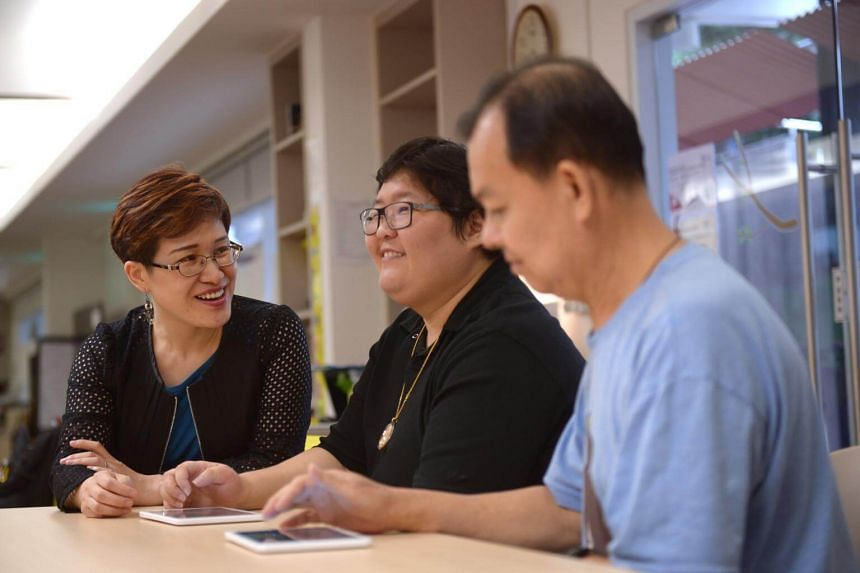 Dr Catherine Dong (left), a visiting neuropsychologist at the National University Hospital Memory Clinic, showing stroke survivors Denise Hu (centre) and Liew Teck Chye how a memory training activity is done at the Enabling Village.