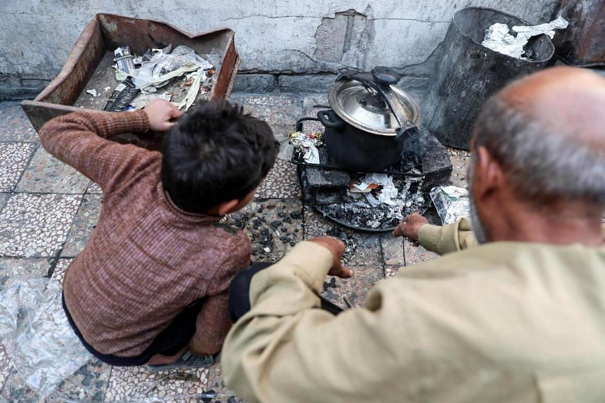 A boy sits next to his grandfather as he uses paper waste to light a cooking fire in Syria, on Oct 18, 2017.