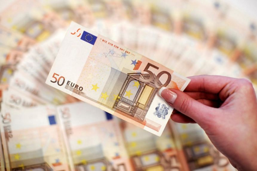 The euro dropped 1.35 per cent to US$1.1653 after the ECB said it would cut its bond purchases in half to 30 billion euros a month from January.