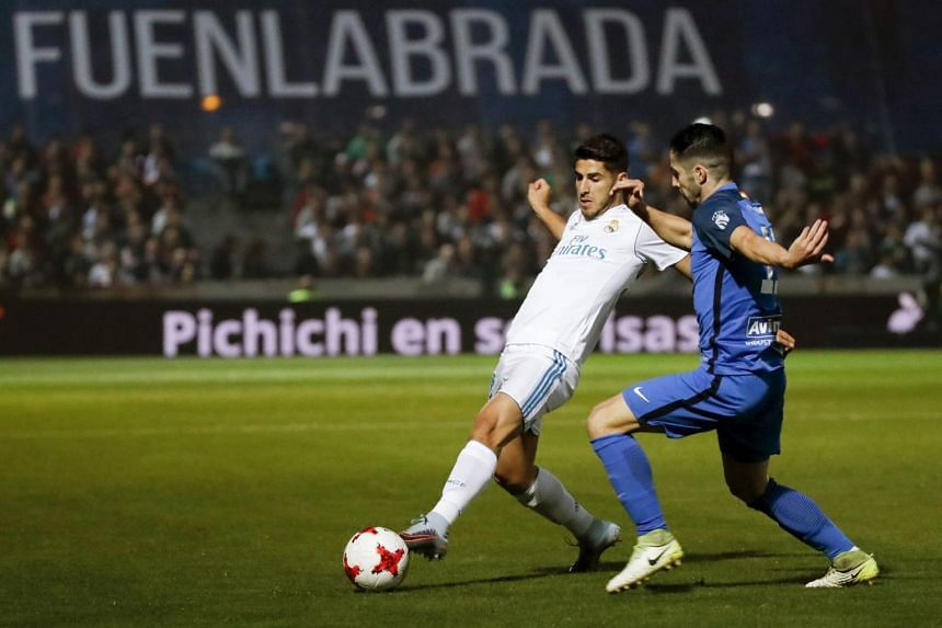 Real Madrid's midfielder Marco Asensio (left) and Fuenlabrada's midfielder Hugo Fraile vie for the ball.