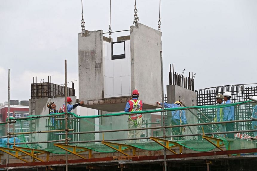 Workers installing a Prefabricated Bathroom Unit (PBU) at a site. More projects have adopted some form of advanced prefab technology from 10 per cent to 40 per cent.