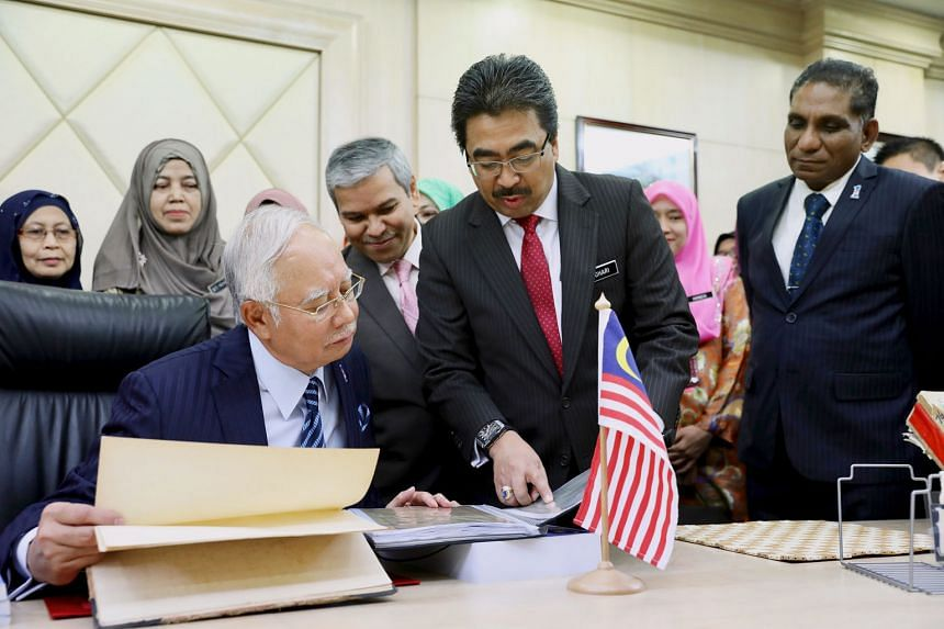 Malaysia's Prime Minister Najib Razak observing last-minute preparations for the 2018 Budget that he will present today. With him is Second Finance Minister Johari Abdul Ghani (in foreground). Datuk Seri Najib said he will start his speech 30 minutes