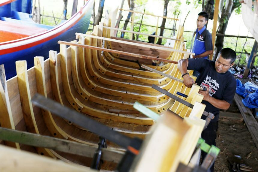Acehnese workers working on a traditional boat using timber in Banda Aceh, Indonesia. The price of timber in the local market has increased significantly due to tightening controls over the timber trade in Indonesia. South-east Asian countries are be