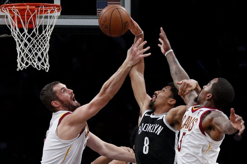 The Nets' Spencer Dinwiddie (No. 8) attempts a basket amid the close attention of the Cavaliers' Kevin Love (left) and J.R. Smith. Dinwiddie hit Brooklyn's go-ahead three as Cleveland conceded 17 three-pointers for the third game in succession.