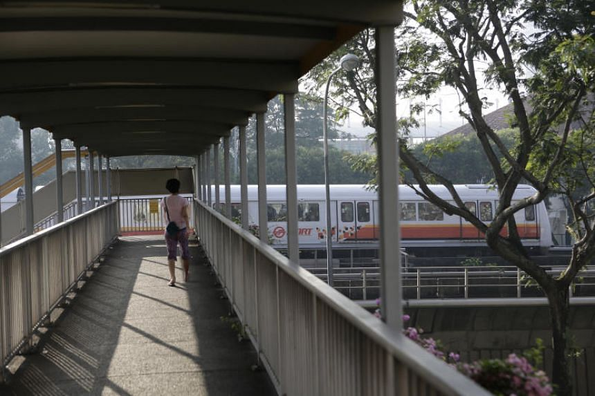 A train travelling along the track near an overhead bridge between Bishan and Ang Mo Kio stations on Oct 25, 2017.