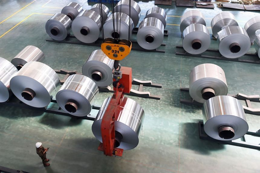 An employee looks at an aluminium foil roll being lifted at a plant in Binzhou, Shandong province, China.