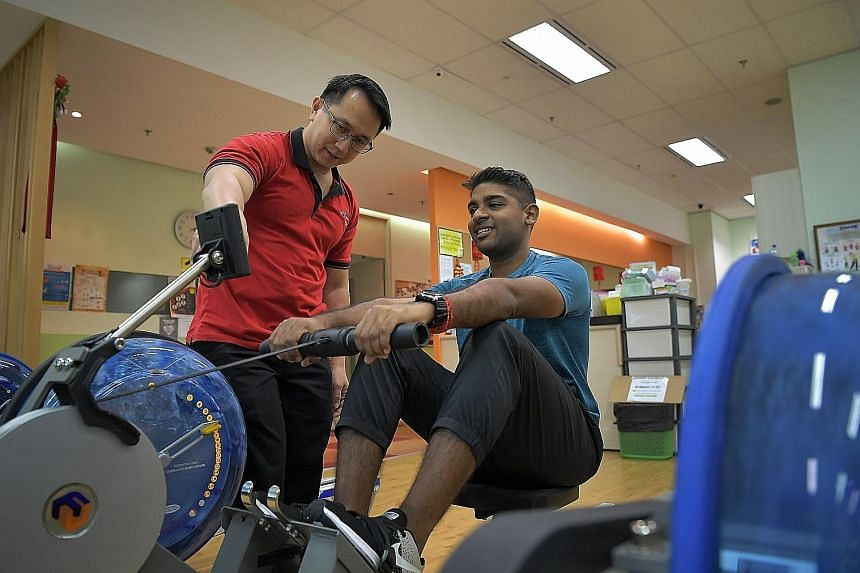Mr Sathish Panirchelvam using a rowing machine at the wellness centre as principal physiotherapist Tay Hung Yong supervises him.