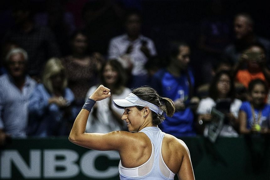 Caroline Garcia of France is overjoyed after beating Caroline Wozniacki of Denmark in their final round-robin match at the WTA Finals. She made the last four as group winner despite being the last - and lowest ranked - to qualify.