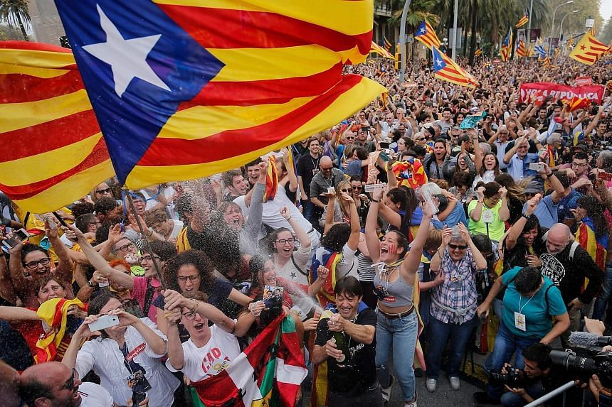 People celebrating in Barcelona yesterday after Catalonia's Parliament voted to declare independence from Spain, despite a walkout by opposition MPs who refused to consider the resolution.