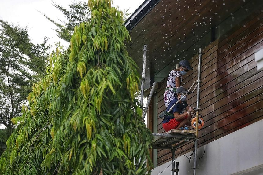Maids who are employed at a Cluny Park residence working on the facade of the two-storey house yesterday.