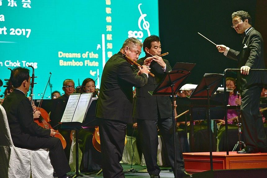 Musicians (standing from far left) Phang Thean Siong and Lim Sin Yeo playing the dizi while music director Tsung Yeh conducts the Singapore Chinese Orchestra at the gala event yesterday.