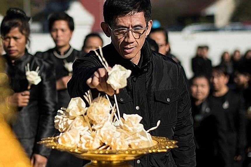 A mourner laying flowers for King Bhumibol Adulyadej at a Buddhist temple in Gretzenbach, Switzerland, on Thursday.