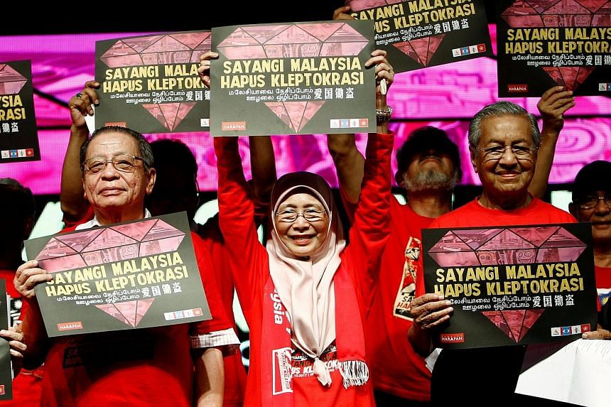 """Opposition leaders (from left) Lim Kit Siang, Wan Azizah and former prime minister Mahathir Mohamad with placards reading """"Love Malaysia, End Kleptocracy"""" at a rally in Petaling Jaya earlier this month."""
