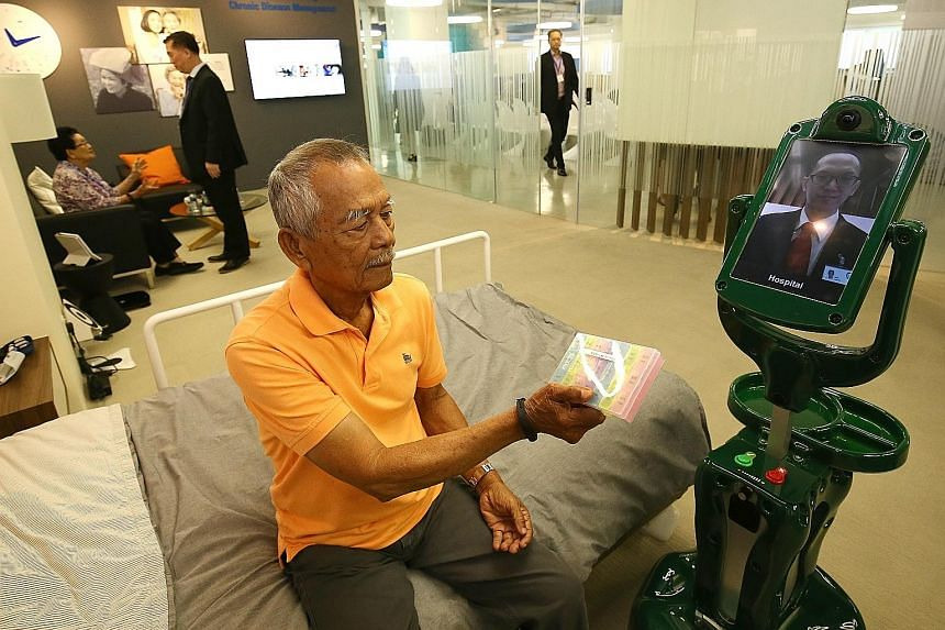 Mr Rasip Bin Sajak, 82, interacting with a robot at TUV SUD's new Smart Elderly Care @ Home Centre.