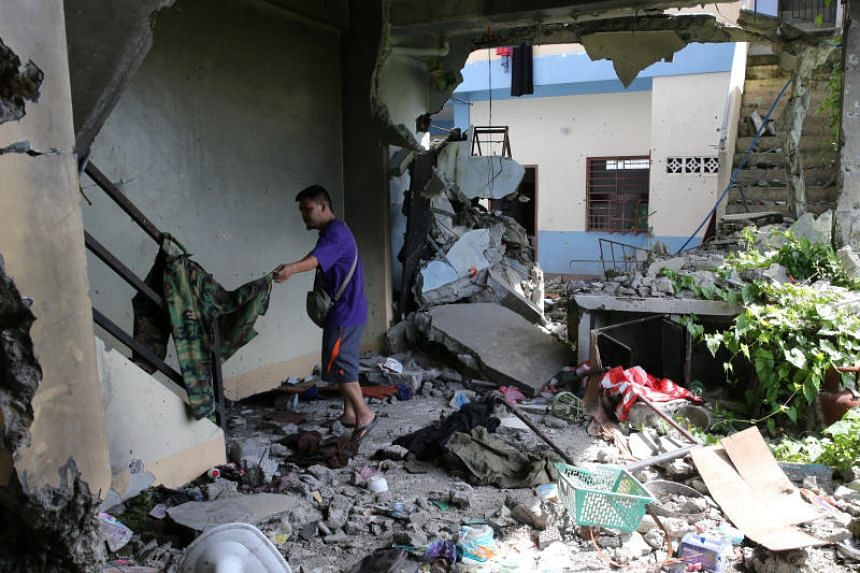 A security force member inspects personal belongings inside a damaged apartment in Malutlut district, Marawi city, on Oct 27, 2017. The apartment was believed to have been rented by pro-ISIS militant group leaders Isnilon Hapilon and Omar Maute befor
