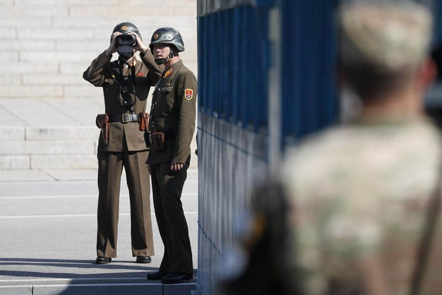 A North Korean soldier looks through binoculars toward South Korea at the Joint Security Area on the Demilitarised Zone in the border village of Panmunjom in Paju, South Korea on Oct 27, 2017.